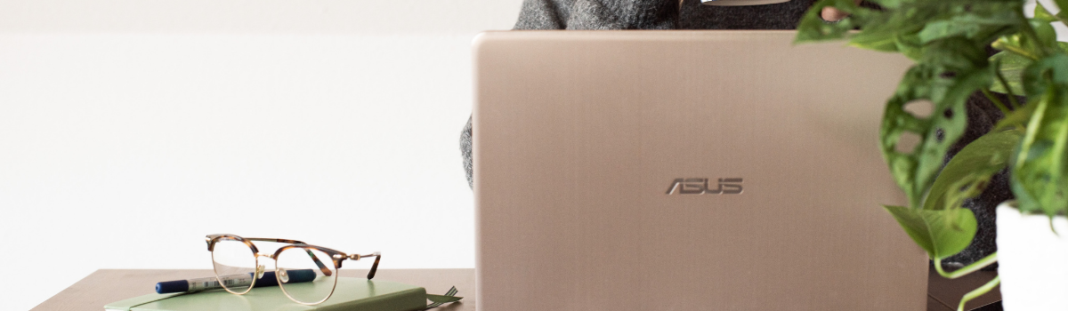 Eine Person sitzt am Laptop. Fokus ist auf dem Laptop.